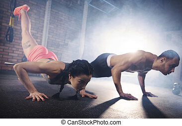 Determinated couple doing plank pose