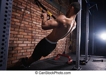 Muscular man pulling resistance bands