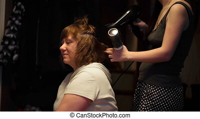 hairdresser dries the hair dryer middle-aged woman closeup
