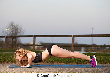 Push ups or press ups exercise by young woman - Girl working...