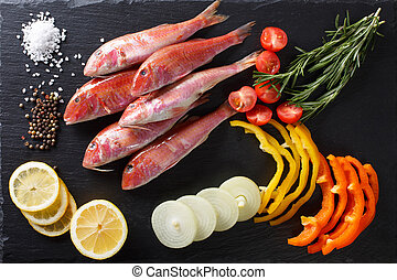 Raw fish red mullet with vegetables and lemon on the table....