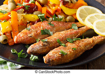 Fried mullet with stewed vegetables and lemon close-up....