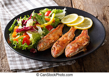 Delicious fried fish red mullet with fresh salad closeup....