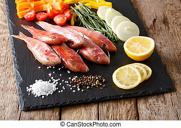 Raw fish red mullet with fresh vegetables and spices...