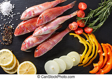 Raw fish red mullet with ingredients close-up on the table....