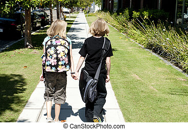 Two Kids Walking to School - Two elementary age kids with...