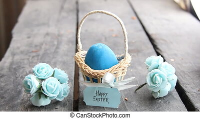 Happy easter. Egg on rustic table and a basket with a blue label