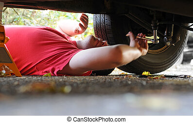 Mechanic working on a car - A white Caucasian male mechanic...