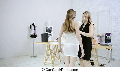 dressmaker takes measurements with woman for sewing dresses in studio