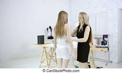 dressmaker takes measurements woman for sewing clothes in studio