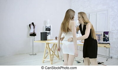 Seamstress takes measurements from mannequin inside atelier.