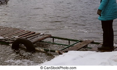 Woman walking dangerously on a destroyed icy pier on the...
