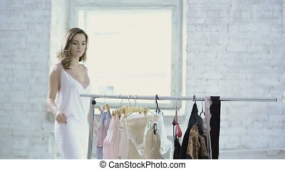 Woman in white nightie comes to rack with hangers to choose...