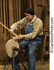 man sharpening an axe on a grinding stone - man sharpening...