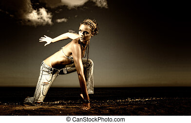 Beautiful young sexy fashion model in jeans by the sea in...