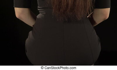 Rear view of young woman wearing sexy short black bodycon...