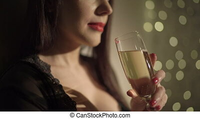 Sexy woman in black lingerie holding champagne glass over holiday highlights