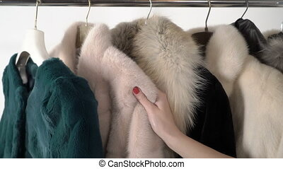 Fur coats and jackets on hanger rack female hand stroking...