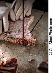 Male butcher's hand slicing meat - Male butcher's hand...
