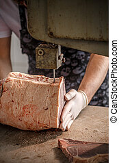 Worker cuts beef meat - Worker cuts onto equal pieces frozen...