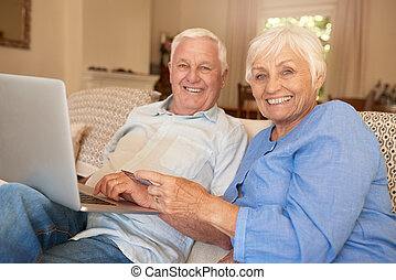 Smiling seniors sitting at home shopping online with a laptop