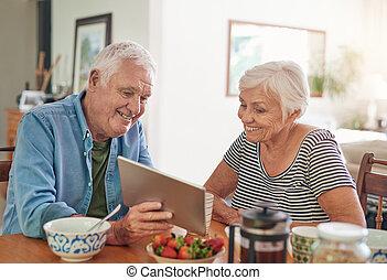 Smiling seniors using a digital tablet together over...