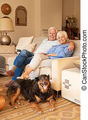 Happy senior couple relaxing with their dog at home -...