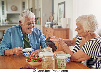 Smiling senior woman pouring her husband a coffee over...