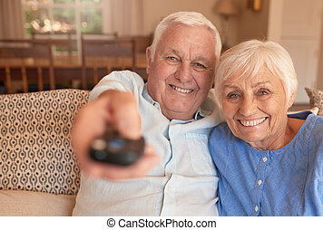 Smiling senior couple changing television channels with a...