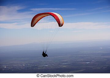 Paraglider flies in the blue summer sky