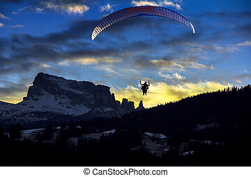 Paraglider flies in the blue winter sky