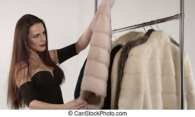 Young woman choosing fur jacket on clothing rack with...