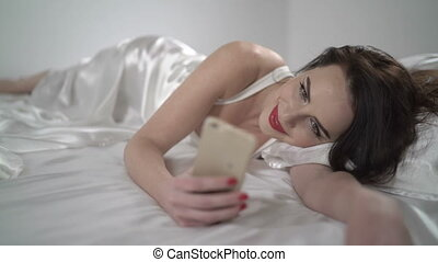 Beautiful brunette woman lying on white silk bed using smartphone