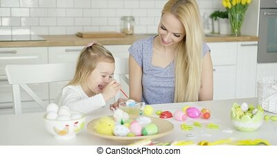 Young female and little girl painting eggs - Beautiful woman...