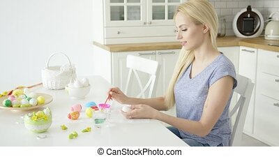 Young girl painting eggs at kitchen - Young beautiful blonde...