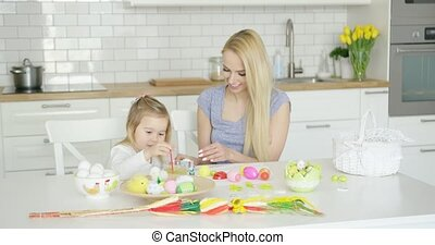 Loving mother and daughter coloring eggs - Charming woman...