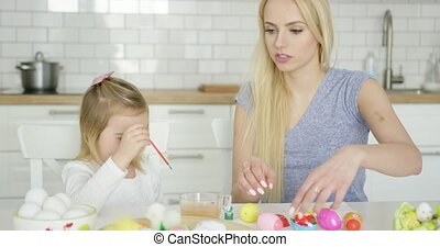 Cheerful girl painting eggs with mother - Laughing little...