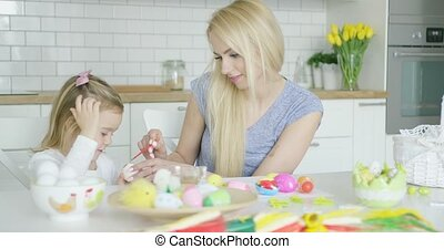 Laughing family coloring eggs