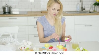 Beautiful girl painting on Easter eggs - Attractive young...