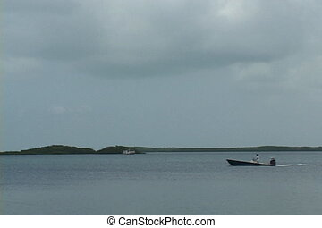 Motorboat - Small motored fishing boat moves across a bay in...