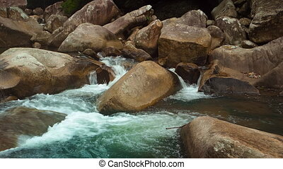 Mountain river flowing between large stones. Static shot...