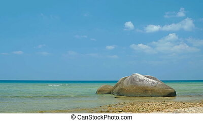 Static video shot - tropical ocean beach with rock in foreground