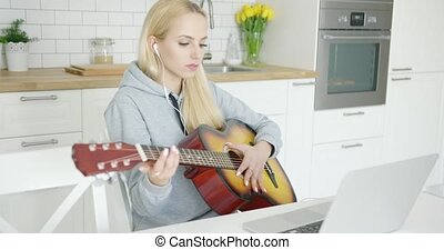 Girl practicing guitar and using laptop - Young wonderful...