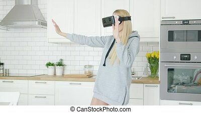 Woman in VR glasses in kitchen - Young female wearing sweat...