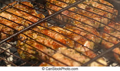 Meat is fried on coals. Close-up with panning - Meat is...