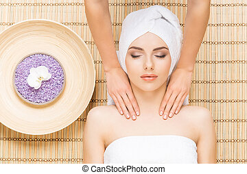 Beautiful, young and healthy woman on bamboo mat in spa salon having face massage. Spa, health and healing concept.