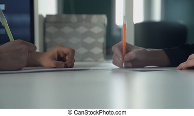 The hands of women quickly write write pen on paper during...