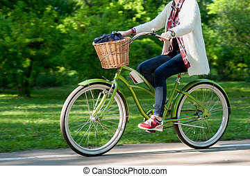 girl making a ride on bisycle in summer park