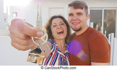 Happy young couple with keys to new home. Property concept