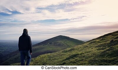 Man Walks Over Hilltop At Sunset - Man walking on hill in...